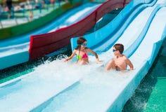 Children in aqua park. Two kids on water slide in aqua park stock images