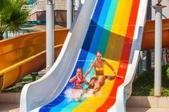 Children at aquapark slide down water slides. Stock Photos
