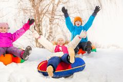 Children with arms high sliding down on the tubes. During frost winter day together Stock Photos