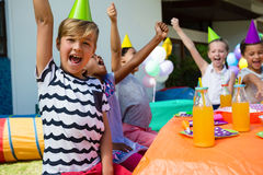 Children with arms raised shouting during party Stock Images