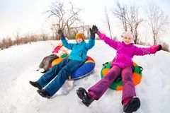 Children with arms up sliding down on the tubes. Together during beautiful winter day with trees trunks on the background Stock Photography
