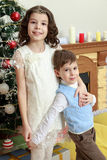 Children around the Christmas tree. Brother and sister hugging each other around the Christmas tree. Boy and girl very happy Royalty Free Stock Images