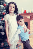 Children around the Christmas tree. Brother and sister hugging each other around the Christmas tree. Boy and girl very happy.Creative toning of a photograph Stock Photo
