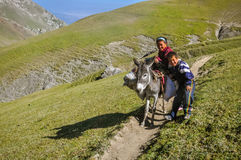 Children in Arslanbob in Kyrgyzstan. Arslanbob, Kyrgyzstan - circa July 2011: Smiling native children pose with donkey at top of hill in mountain range of Royalty Free Stock Photography