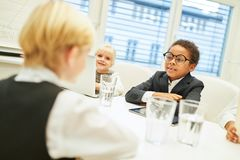Children as business people in a meeting. Negotiating a multicultural joint venture stock image