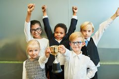 Children as business start-up team with winner`s trophy. Multicultural children as a business start-up team with a winner`s cup of cheering royalty free stock image