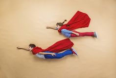 Children as superheroes. Children are playing as superheroes with red coats Royalty Free Stock Image
