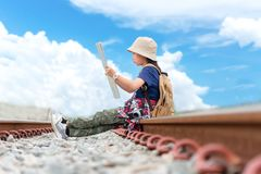 Children asian girl holding maps with camera and travel backpacks sitting in the railroad. Travel Concept royalty free stock images