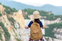 Children asian girl holding maps and travel backpacks standing in the mountain. Travel Concept royalty free stock photos