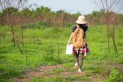 Children asian girl walking and holding maps and travel backpacks in the forest for education nature. Travel Concept royalty free stock photos