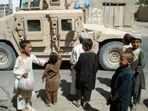 Children asking for food from the US soldiers. Group of seven children from Afghanistan asking for food from the US soldiers royalty free stock photos