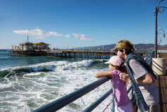 Children atching from the pier. Brother holds his sister as they watch the waves from the end of the pier royalty free stock image