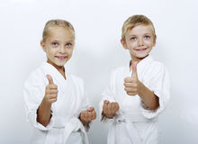 Children athletes with belts show thumb super Royalty Free Stock Photo