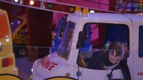 Children attraction. Little girl riding on a child train in game park in the mall center. Ride the ambulance car stock footage