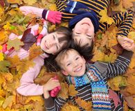 Children in autumn leaves. Three siblings laying in autumn leaves Stock Photos