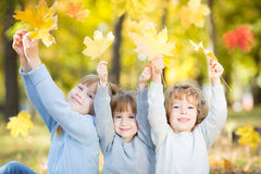 Children in autumn park. Happy children with maple leaves in autumn park royalty free stock images