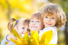 Children in autumn park. Happy children with maple leaves in autumn park stock photo