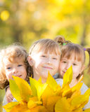 Children in autumn park. Happy children with maple leaves in autumn park royalty free stock photography