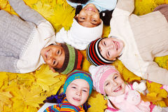 Children on autumnal leaves Royalty Free Stock Images