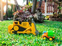 Children baby toys tractor and truck in the beautiful garden forest playground outdoor. Children baby toys tractor and truck in the beautiful garden forest Stock Photo