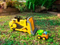 Children baby toys tractor and truck in the beautiful garden forest playground outdoor. Children baby toys tractor and truck in the beautiful garden forest Royalty Free Stock Photos
