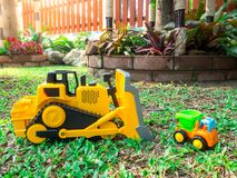Children baby toys tractor and truck in the beautiful garden forest playground outdoor. Children baby toys tractor and truck in the beautiful garden forest Royalty Free Stock Images