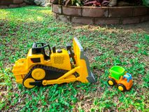 Children baby toys tractor and truck in the beautiful garden forest playground outdoor. Children baby toys tractor and truck in the beautiful garden forest Stock Photography