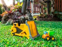 Children baby toys tractor and truck in the beautiful garden forest playground outdoor. Children baby toys tractor and truck in the beautiful garden forest Royalty Free Stock Photography