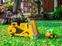 Children baby toys tractor and truck in the beautiful garden forest playground outdoor. Children baby toys tractor and truck in the beautiful garden forest Stock Image