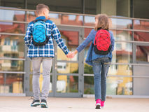 Children back to school. Happy children - boy and girl with books and backpacks on the first school day. Young students beginning of class after vacation. Full Stock Photos