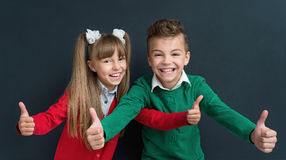 Children back to school. Happy pupils - boy and girl, showing thumbs up gesture in front of a big chalkboard. Back to school concept Royalty Free Stock Image