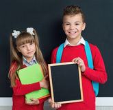 Children back to school. Happy pupils posing together in front of a big chalkboard. Back to school concept Stock Photos