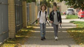 Children with backpacks come back from school and smiling. Teen boy holding to hand girl and walking at park outdoors. stock footage