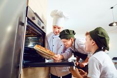 Children bakers with pizza in the kitchen with a cook royalty free stock images