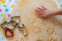 Children Baking Christmas Cookies cutting pastry. Children baking Christmas cookies: Cutting pastry with a cookie cutter on a colorful table cloth Royalty Free Stock Photos