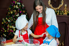 Children baking christmas cookies. Kids baking christmas cookies before the celebration of Christmas. Family Stock Photography