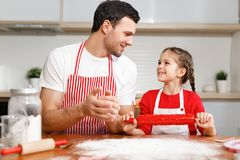 Children, baking, family concept. Cheerful brunet male wears apron and kneads dough, happy girl holds rolling pin, ready. To help her father, sit together at Royalty Free Stock Photography