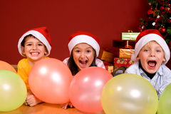Children with ballons by Christmas tree. Laughing Children playing with ballons by Christmas tree in red room Royalty Free Stock Photography