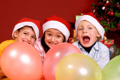 Children with ballons by Christmas tree Stock Photo