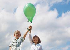 Children with balloon. Happy sister and brother with balloon on the sky background Royalty Free Stock Photography