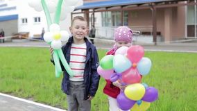 Children with balloons in the form of flowers. Handsome boy and a girl standing outdoors. Holiday concept stock video