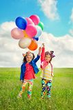 Children with balloons walking on spring field Royalty Free Stock Photography