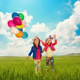 Children with balloons walking on spring field royalty free stock photos