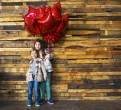 Children with balloons at wooden wall Stock Photos