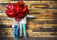 Children with balloons at wooden wall Royalty Free Stock Images