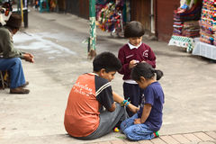 Children in Banos, Ecuador. BANOS, ECUADOR - FEBRUARY 25, 2014: Unidentified children on pavement at the Pasaje Artesanal (Artisan Passage) on February 25, 2014 Stock Photo