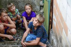 Children in the basement, three boys and a girl near the iron door are hiding on the steps from the outside world. Post-production. Photo royalty free stock photography