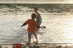 Children bathe in the evening on the city beach Royalty Free Stock Photography