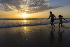 Children bathing on the beach at dusk Stock Image
