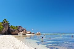 Children bathing on La Digue. A group of children playing in the turquoise waters of the Indian Ocean at the shore of famous Source d'Argent beach on La Digue Royalty Free Stock Photo